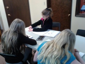 Three IA students work carefully on their creations,